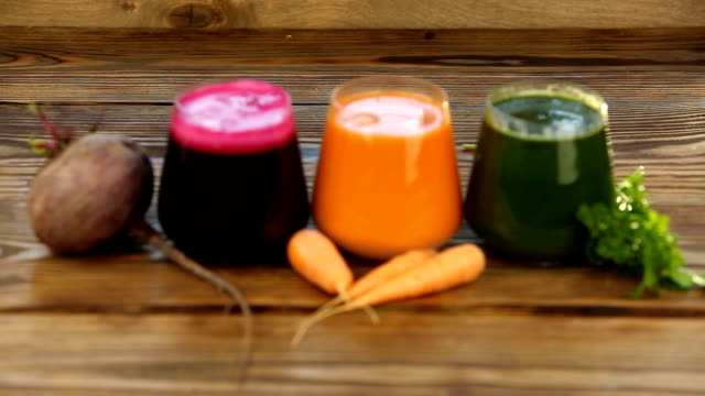 three vegetable juice in glass cup on wooden background video