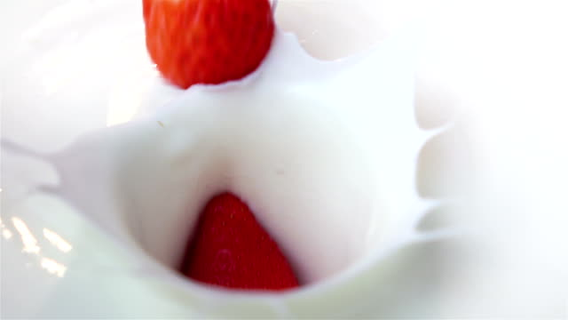 Three videos of strawberries falling into yogurt -real slow motion video