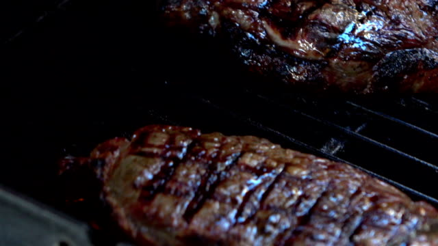 Three videos of turning over steaks on the grill-slow motion video