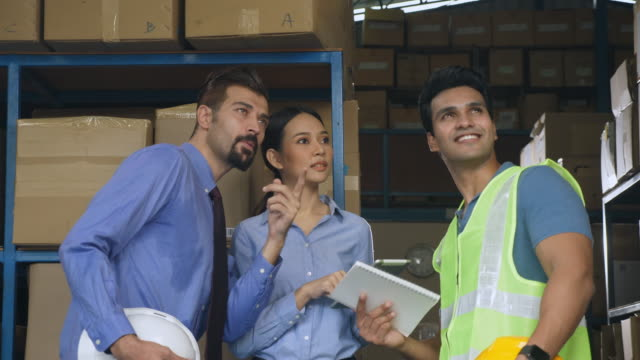 Three warehouse workers meeting and discussing together