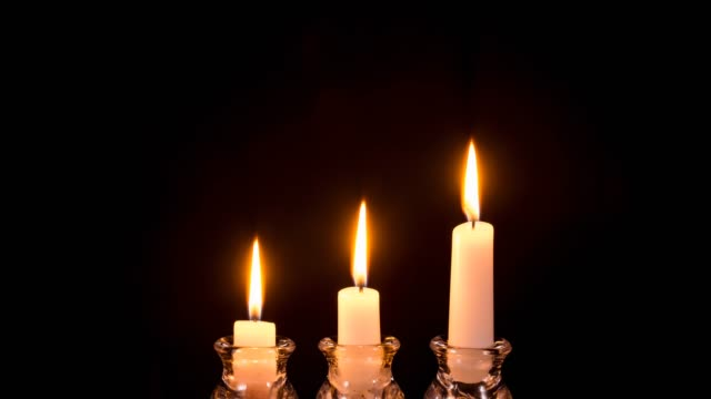 Three white candles burning out