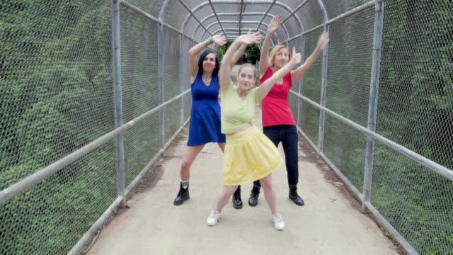 tre kvinnor dansar i en bur bro omgiven av träd - blue yellow band bildbanksvideor och videomaterial från bakom kulisserna