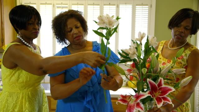 three women helping with a flower arrangement