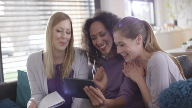 Three women laughing at something on a digital tablet Medium handheld shot of three women looking at something on the digital tablet and laughing. Shot in Slovenia. only young women stock videos & royalty-free footage