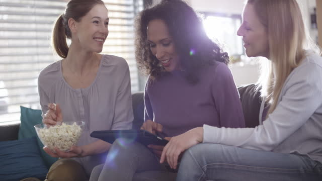 Three women laughing while scrolling on a digital tablet Medium handheld shot of three women laughing and talking while using a digital tablet. Shot in Slovenia. only young women stock videos & royalty-free footage
