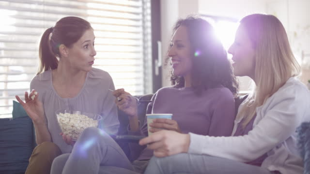 three women laughing while watching tv and eating popcorn - amicizia tra donne video stock e b–roll