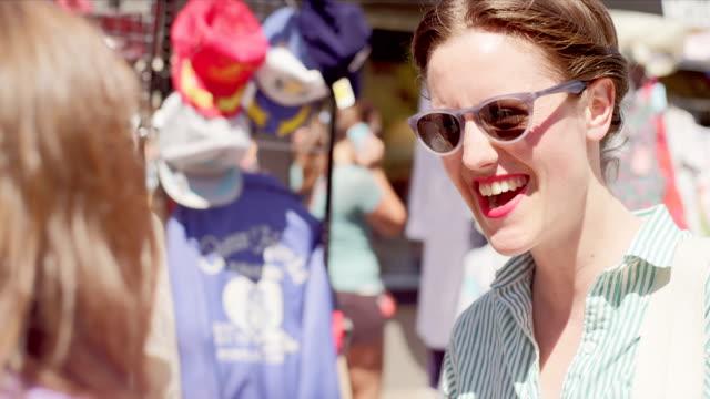 vídeos de stock, filmes e b-roll de três mulheres para comprar roupas em um mercado ao ar livre - arméria