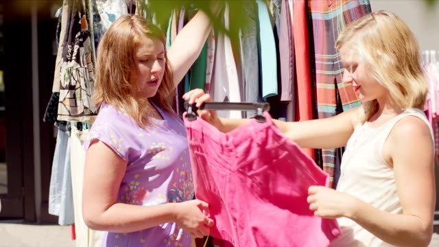 Three women shopping for clothes at an outdoor market video