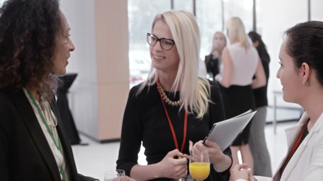 tre kvinnor talar i lobbyn på en konferenssal - affärskonferens bildbanksvideor och videomaterial från bakom kulisserna