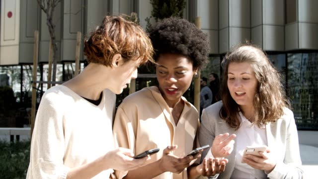 Three women with smartphones sitting on street