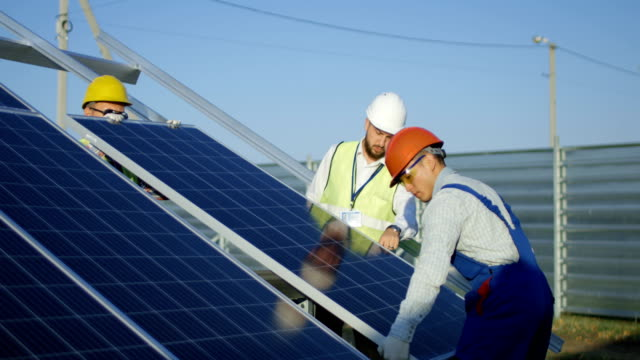 Three workers install a solar panel video