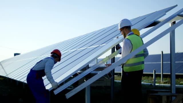 3 노동자는 태양 전지 패널 설치 - 태양 에너지 스톡 비디오 및 b-롤 화면