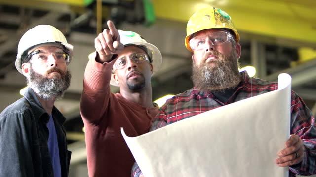 drei arbeiter tragen schutzhelme, pläne zu betrachten - halle gebäude stock-videos und b-roll-filmmaterial