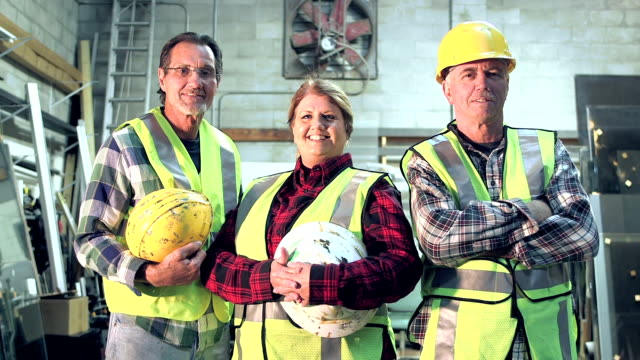 Three workers with hardhats and safety vest - video