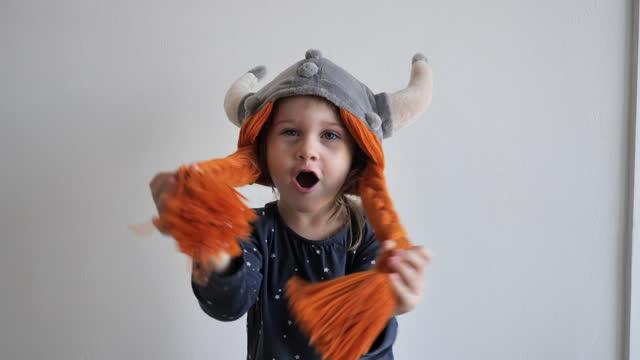vídeos y material grabado en eventos de stock de niña de tres años jugando en casa, disfrazada de sombrero vikingo y peluca - vikingo