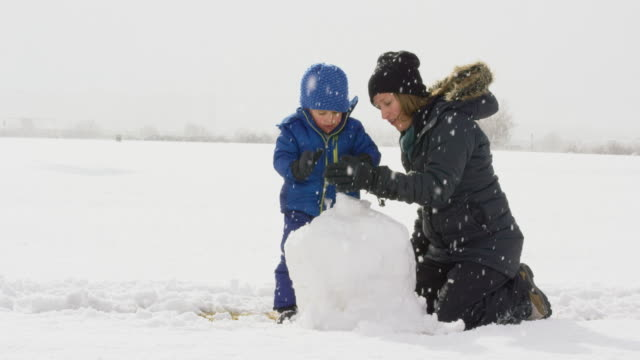 vídeos de stock e filmes b-roll de three year-old caucasian boy and his caucasian mother in her thirties (both dressed in winter clothing) make a snowman together on a snowy, overcast day - roupa quente