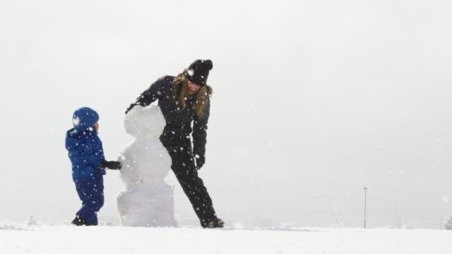 vídeos y material grabado en eventos de stock de muchacho caucásico tres años y su madre caucásica treintañera (ambos vestidos con ropa de invierno) hacer un muñeco de nieve junto a un nevado, nublado el día - snowman
