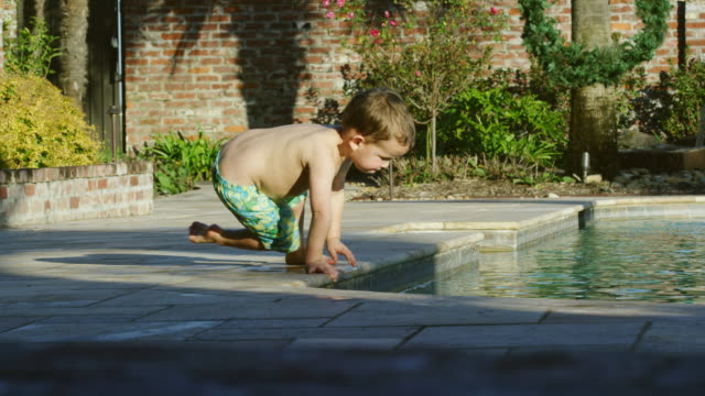 a three year-old caucasian boy crawls to the edge of a swimming pool and puts his hand in the water on a sunny summer day - curiosità video stock e b–roll