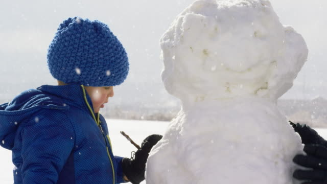 Three Year-Old Caucasian Boy Dressed in Winter Clothing Puts Stick Arms on a Snowman on a Snowy Day Three Year-Old Caucasian Boy Dressed in Winter Clothing Puts Stick Arms on a Snowman on a Snowy Day snowman stock videos & royalty-free footage