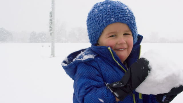 Three Year-Old Caucasian Boy Dressed in Winter Clothing Rolls a Snowball on the Ground and Picks It Up on a Snowy, Overcast Day Three Year-Old Caucasian Boy Dressed in Winter Clothing Rolls a Snowball on the Ground and Picks It Up on a Snowy, Overcast Day snowman stock videos & royalty-free footage