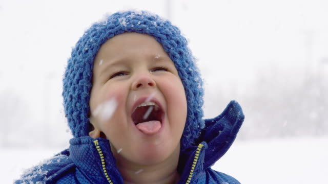 three year-old caucasian boy dressed in winter clothing tries to catch snowflakes on his tongue on an overcast day - lingua bocca video stock e b–roll