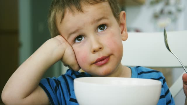 ein drei jahre alter kaukasischer junge isst macaroni und cheese pasta von einem bowl mit einem löffel an einem küchentisch in innenräumen, während smiling - 2 3 jahre stock-videos und b-roll-filmmaterial