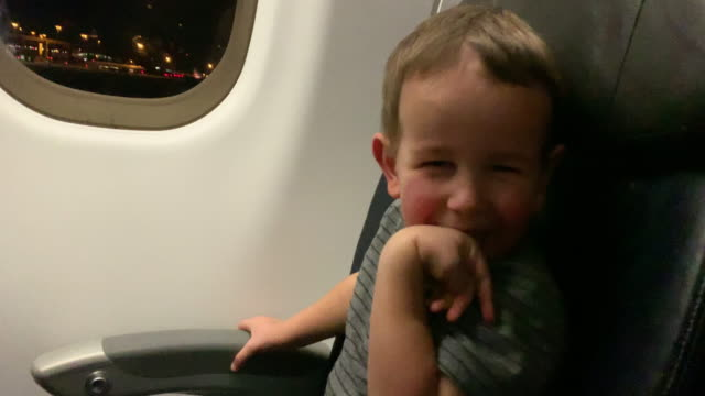 A Three Year-Old Caucasian Boy Looks Out the Window of a Commercial Airliner Jet Passenger Plane and Laughs at the Camera while a Five Year-Old Caucasian Boy and His Thirty-Something Caucasian Mother Also Enjoy Taking Off on an Airplane at Night