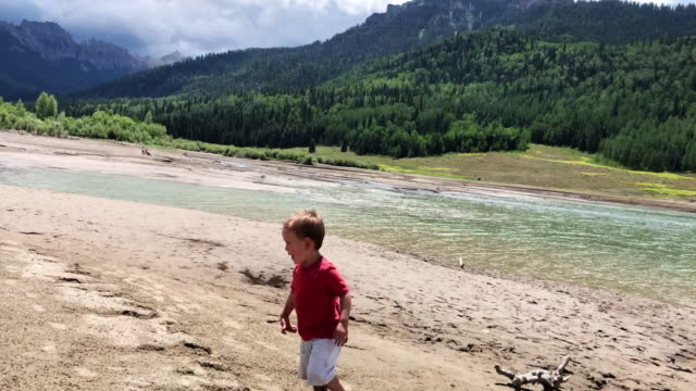 A Three Year-Old Caucasian Boy Runs around on the Sand Next to a Mountain Lake Surrounded by Forests and Storm Clouds in the Rocky Mountains of Colorado in Summer on an Overcast Day