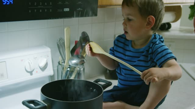 a three year-old caucasian boy sitting on the counter in the kitchen pulls a wooden spoon out of a pot of hot water on the stove top range and recoils after he feel it is hot - niebezpieczeństwo filmów i materiałów b-roll