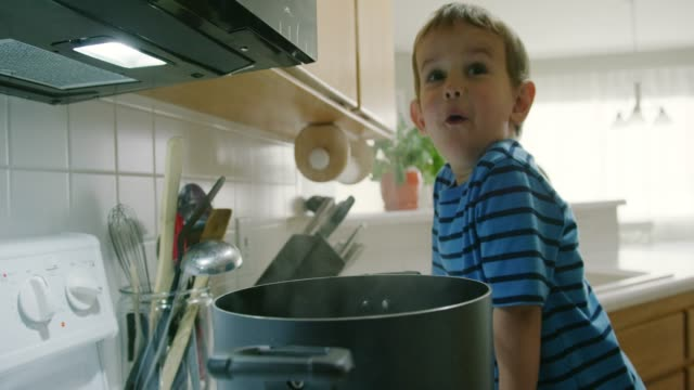 vídeos de stock e filmes b-roll de a three year-old caucasian boy talks while looking into a steaming pot that is sitting on a stove top range in a kitchen - cooker happy