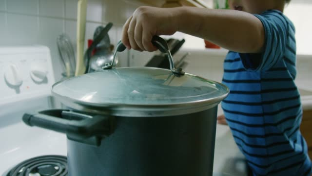 a three year-old caucasian boy talks while placing a glass lid on to a steaming pot that is sitting on a stove top range in a kitchen - coperchio video stock e b–roll