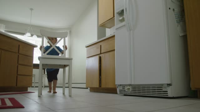 a three year-old caucasian boy walks into the kitchen, slides a chair over to a cabinet, and climbs on to the chair to get something out of the cabinet - мозаика стоковые видео и кадры b-roll