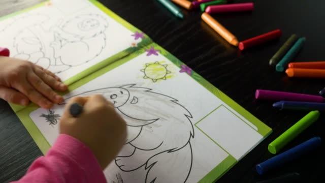 ein dreijähriges kind malt ein buch mit farbigen buntstiften - ameisenbär stock-videos und b-roll-filmmaterial