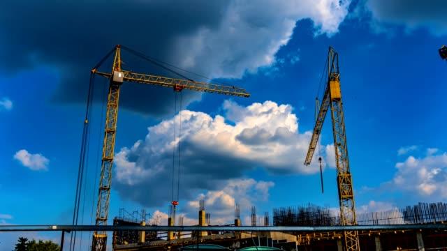 tre gula konstruktions kranar arbete på plats av en byggnad under konstruktions tid förfaller - blue yellow bildbanksvideor och videomaterial från bakom kulisserna
