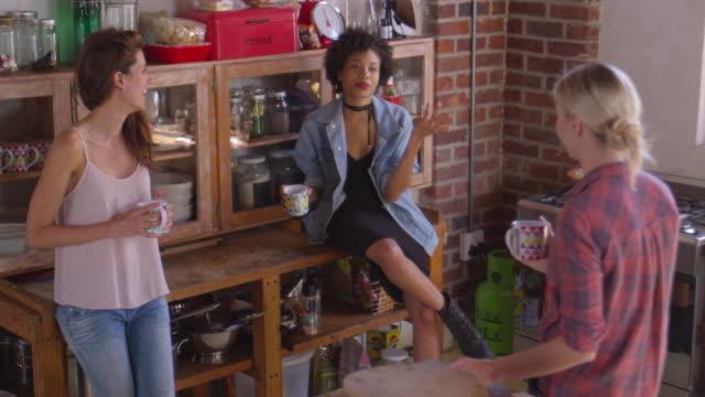 Três jovens adultas namoradas conversar na cozinha, vista elevada, filmado em R3D - vídeo