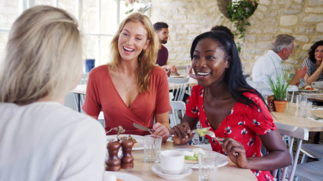 Three young adult women having brunch together and talking in a small restaurant, waist up Three young adult women having brunch together and talking in a small restaurant, waist up girlfriend stock videos & royalty-free footage