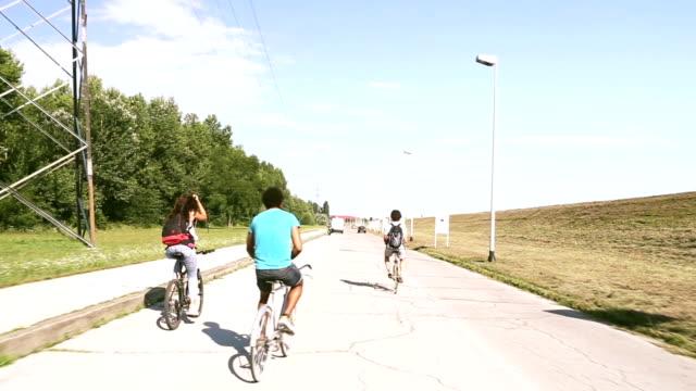 Three young adults having fun cycling video
