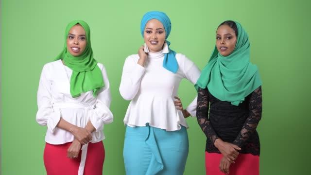 tre unga afrikanska muslimska kvinnor tillsammans mot färgnyckel med grön bakgrund - hijab bildbanksvideor och videomaterial från bakom kulisserna