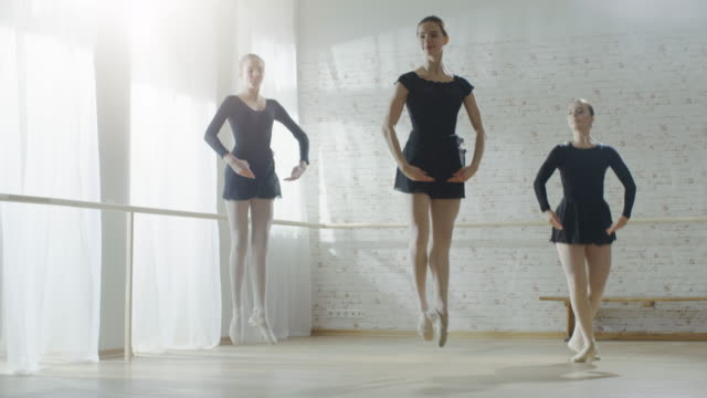 three young and gorgeous ballerinas synchronously dancing and jumping in slow motion. shot on a sunny morning in a bright and spacious studio. - balet filmów i materiałów b-roll