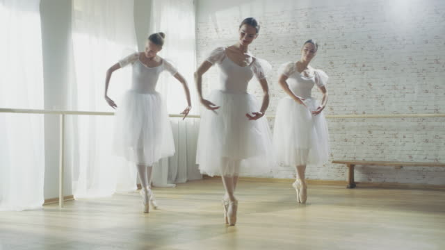 vídeos de stock e filmes b-roll de three young and gorgeous ballerinas synchronously dancing. they wear white tutu dresses. shot on a sunny morning in a bright and spacious studio. - tule têxtil