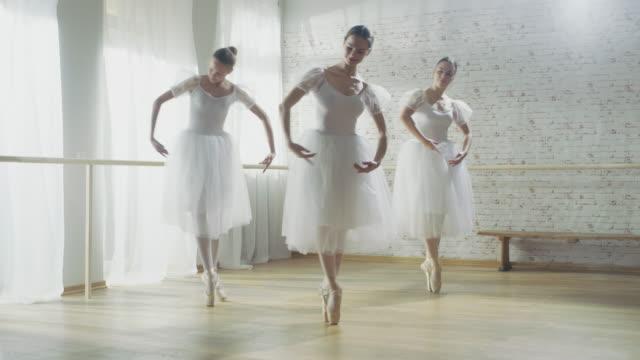 tre unga och gorgeous ballerinas synkront dancing. de bär vita tutu klänningar. sköt på en solig morgon i en ljus och rymlig studio. - piruett bildbanksvideor och videomaterial från bakom kulisserna