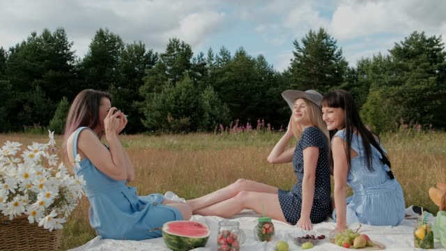 Three young attractive girls on a picnic. The photographer takes pictures on the mirrorless camera of two models. Models pose and watch photos.