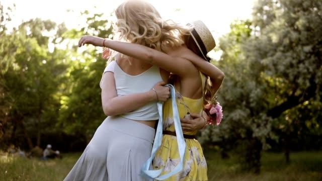 Três mulheres jovens, atraentes, abraçando uns aos outros. Amar amigos. Encontro de amizade. Câmera lenta - vídeo