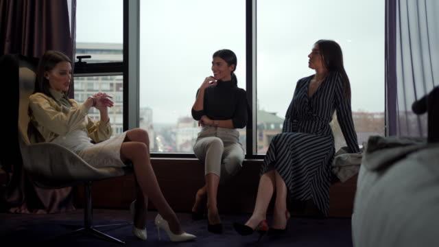stockvideo's en b-roll-footage met drie jonge mooie businesswomen die na een bedrijfsvergadering ontspannen - raam bezoek