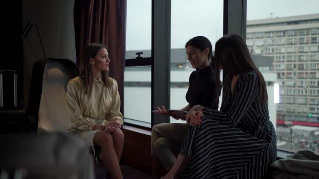 stockvideo's en b-roll-footage met drie jonge zakenvrouwen die in een hotelruimte spreken - raam bezoek