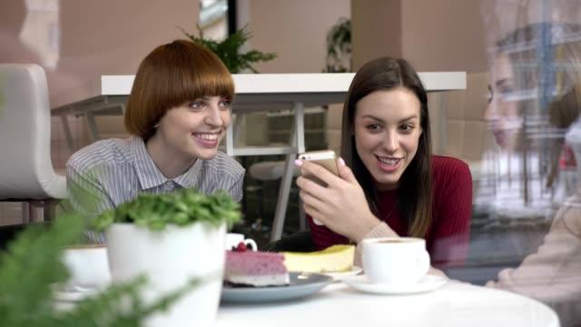 drei junge kaukasische mädchen sitzen im café, lachen, lächeln, freunde, firma, klatsch, dialog, diskussion. freundinnen in der café-konzept. sehen sie ein lustiges video, ein foto mit einem smartphone 60 fps - teenage friends sharing food stock-videos und b-roll-filmmaterial