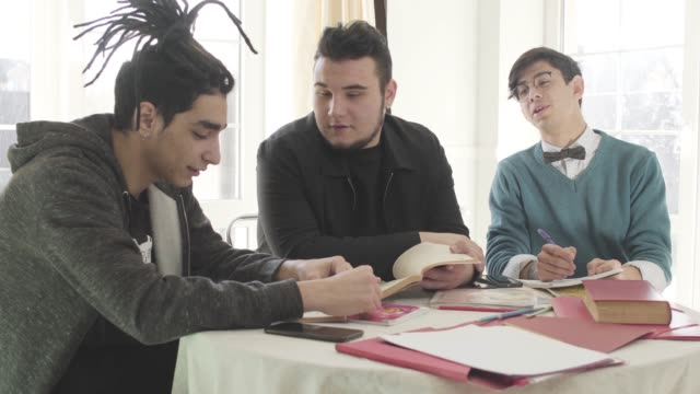 three young caucasian men sitting at the table, talking and laughing. male university students studying together indoors. friends enjoying studies. education concept. - solo bambini maschi video stock e b–roll