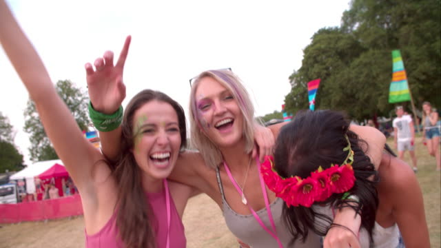 Three young female friends having fun at a music festival video