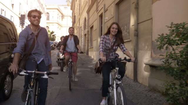 Three young friends tourists riding bikes in small street in Rome city centre on sunny day slow motion camera car steadycam