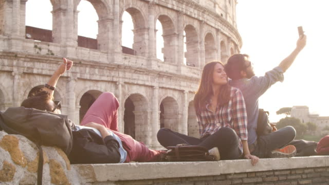 Three young friends tourists sitting in front of colosseum in rome at sunset taking selfies with smartphone with backpacks sunglasses happy beautiful girl long hair slow motion